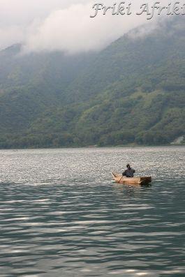 Mężczyźni łowią ryby w małych drewnianych łódkach